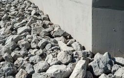 Rock and gravel rubble by smooth gray wall. Stock Photos