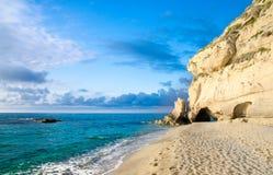 Rock with greenery near sandy beach of Tyrrhenian Sea, Tropea, I stock photo