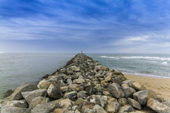 Rock groin jutting out into the Pacific Ocean - California Stock Photo