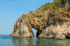 Rock with grot. In a blue sea Stock Photo