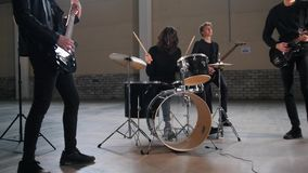 A rock group having a repetition in a hangar. Mid shot stock photography