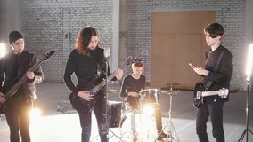 A rock group having a repetition. People in black clothes playing their parts. Mid shot royalty free stock image
