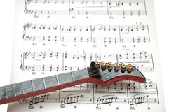 Rock guitar. Over the sheet of printed music Royalty Free Stock Image