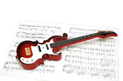 Rock guitar over the sheet. Of printed music Stock Photos
