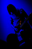 Rock guitarist. Silhouette of a Rock guitarist on stage, cast in the blue light of a directional spot Royalty Free Stock Image