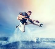 Rock guitarist with bas-guitar, snapshot in a jump. Splashing water on background. Music performer Stock Image