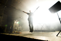 Rock guitarist in midair. A rock guitarist is airborne in a loud concert Stock Photos