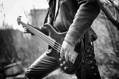 Rock guitarist outdoor. A musician with a bass guitar in a leath. Rock guitarist on the steps. A musician with a bass guitar in a leather suit. Metalist with a Stock Image