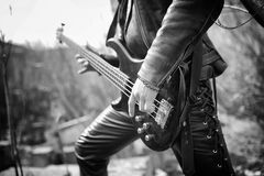 Rock guitarist outdoor. A musician with a bass guitar in a leath. Rock guitarist on the steps. A musician with a bass guitar in a leather suit. Metalist with a Royalty Free Stock Images