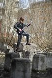 Rock guitarist on the steps. A musician with a bass guitar in a. Leather suit. Metalist with a guitar on the background of industrial step.r stock images