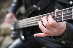 Rock guitarist on the steps. A musician with a bass guitar in a. Leather suit. Metalist with a guitar on the background of industrial step.r stock photos