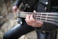 Rock guitarist on the steps. A musician with a bass guitar in a. Leather suit. Metalist with a guitar on the background of industrial step.r stock image
