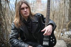 Rock guitarist on the steps. A musician with a bass guitar in a. Leather suit. Metalist with a guitar on the background of industrial step.r stock photography