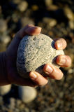 Rock In Hand Closed. A peron holding out a rock in their closed hand Stock Photo