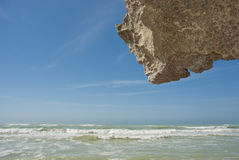 Rock hanging above waves Royalty Free Stock Image