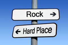 Between a rock and a hard place. Between a rock and a hard place signpost Stock Photo