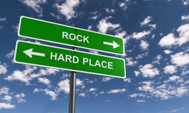 Rock and a hard place. Sign post with two green boards one pointing to 'rock' and the other 'hard place' both in upper case white letters and arrows pointing in Royalty Free Stock Photography