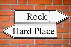 Between rock and hard place signpost concept brick wall stock image