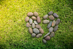 Rock heart shape on a green grasses field. Royalty Free Stock Photos