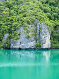 Rock hill reflection on green sea water royalty free stock photography