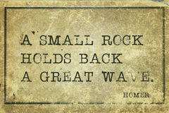 Rock holds Homer. A small rock holds back a great wave - ancient Greek poet Homer quote printed on grunge vintage cardboard Royalty Free Stock Photo