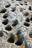 Rock with holes and water. Lots of holes in big rock that are filled with water. Naturally weathered to have a honeycomb pattern Royalty Free Stock Image