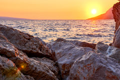Rock island at golden sunset in Brela Stock Images
