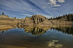 The Rock Island. Reflection of a rock in the middle of Lake Mary in the Wasatch National forest this lake sits above the ski resort Brighton Utah Royalty Free Stock Photos