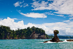 Rock island in the sea with trees and blue sky Stock Photography