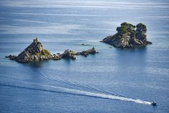Rock islands on the sea off the coast of Croatia with a motorboat sailing along. stock photo