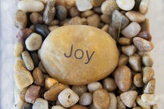 A rock with joy engraved on it. One large rock surrounded by pebbles Stock Photo