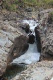 Rock kilade mellan två vaggar framsidor med vatten som rusar runt om den Arkivfoton