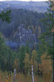 Rock Knight stands in the autumn forest among the trees at sunse Stock Image