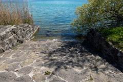Rock-made path down to clear lake water Royalty Free Stock Images