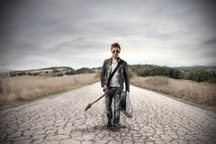 Rock man walking in the street. Handsome rock man with guitar walking in a desert street Royalty Free Stock Photography
