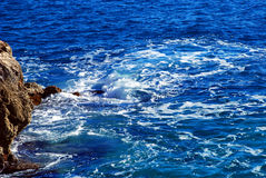 Rock in the Mediterranean Sea. In the blue sea water is splashing at the foot of the rock Stock Image
