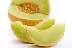 Rock Melon. With 2 slices as closeup on white background royalty free stock photo