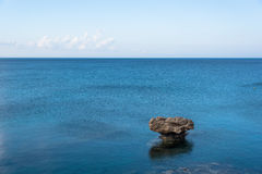 Rock in the middle of blue sea Stock Images