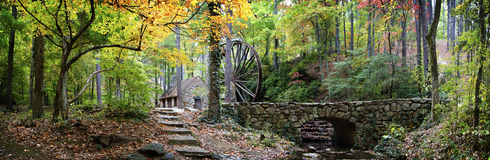 Rock mill and bridge in Autumn. Panoramic of old rock mill hidden in a colorful magical mystical enchanted forest surrounded by the bright vivid leaved of the Royalty Free Stock Photo
