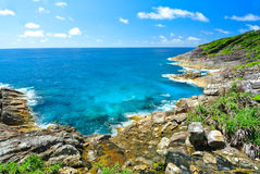 Rock Mountain with Blue Ocean on Blue Sky. On island Stock Photo