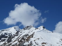 Rock Mountain Covered With Snow Under Blue Sky Stock Photography
