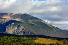 Rock Mountain at Dawn with Trees. A mountain at dawn in the summer with patches of permafrost snow Royalty Free Stock Image
