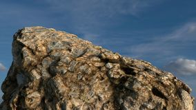 Rock /mountain in front of blue sky. 3D render. Realistic 3D render of a rock /mountain in front of blue sky with clouds Royalty Free Stock Image
