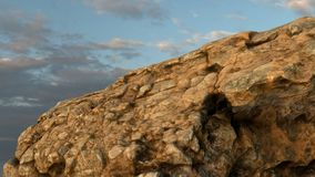 Rock /mountain in front of cloudy sky. Royalty Free Stock Images