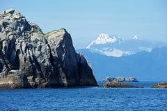 Rock and mountain over ocean Royalty Free Stock Photos