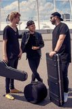 Rock music band with musical instruments in cases having conversation. On street royalty free stock images