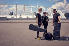 Rock music band with musical instruments in cases having conversation. On street stock images