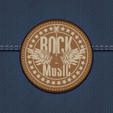 Rock music. Banner with the emblem of rock music and the guitar on the background of denim Royalty Free Stock Image