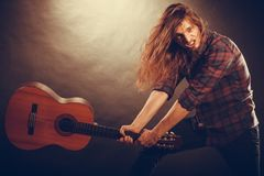 Rock musician destroys his guitar. Rock music energy people feelings concept. Mad rock guitarist destroys his guitar Royalty Free Stock Photography