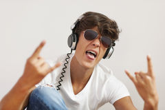 Rock music. Excited young man listening hard rock music stock photography